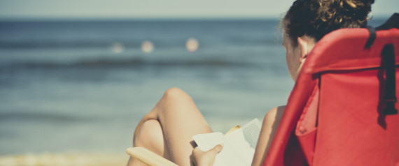 Girl sitting on red chair reading on beach
