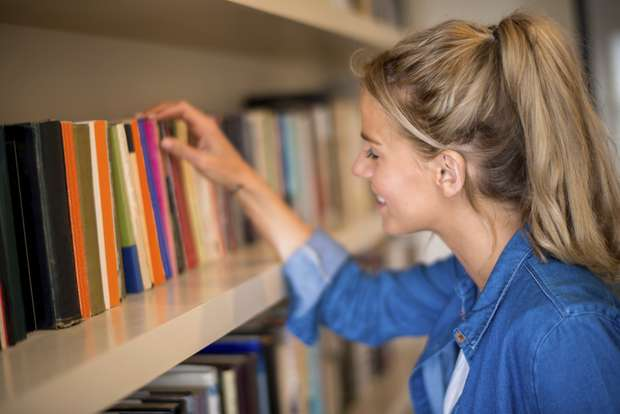 Woman at home taking a book from the library